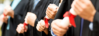 Row of students close up on hands holding graduation diplomas
