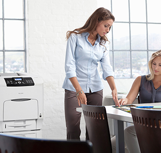 Ricoh Printer in office setting. Two women discussing with paperwork.