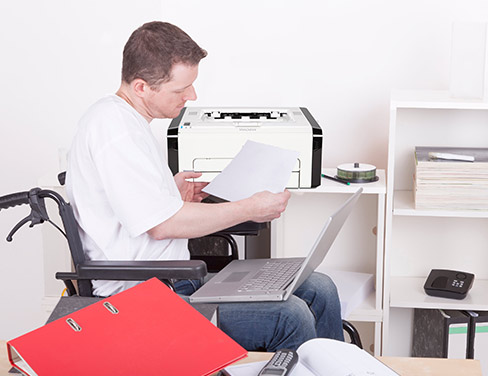 Photo of a man in a wheelchair holding a piece of paper with his laptop in his lap near a printer.