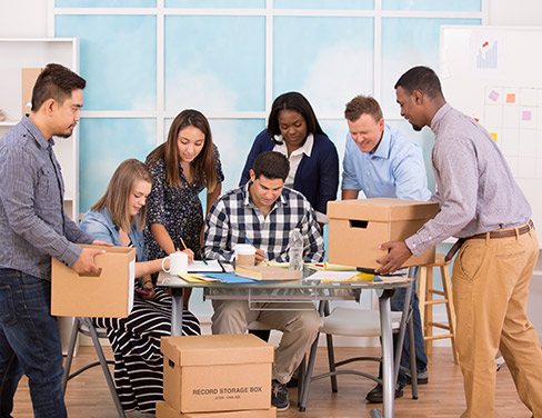 """Photo of a group of people gathered around a table with boxes and documents."""