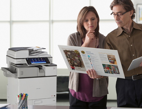 Office employees looking at printed documents.