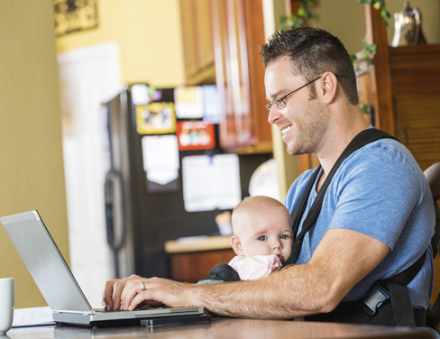 """Father with baby working on a laptop at home."""