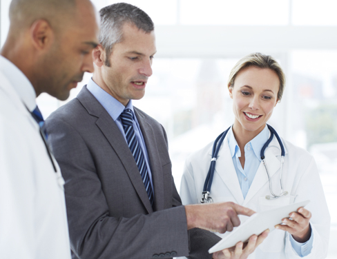Two doctors and a businessman looking at a printed document.