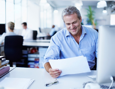 Man sitting at his desk looking at papers