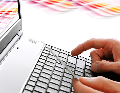 """Close up of hands typing on a laptop"""