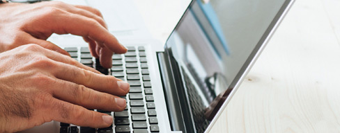 """Closeup of hands typing on a laptop"""